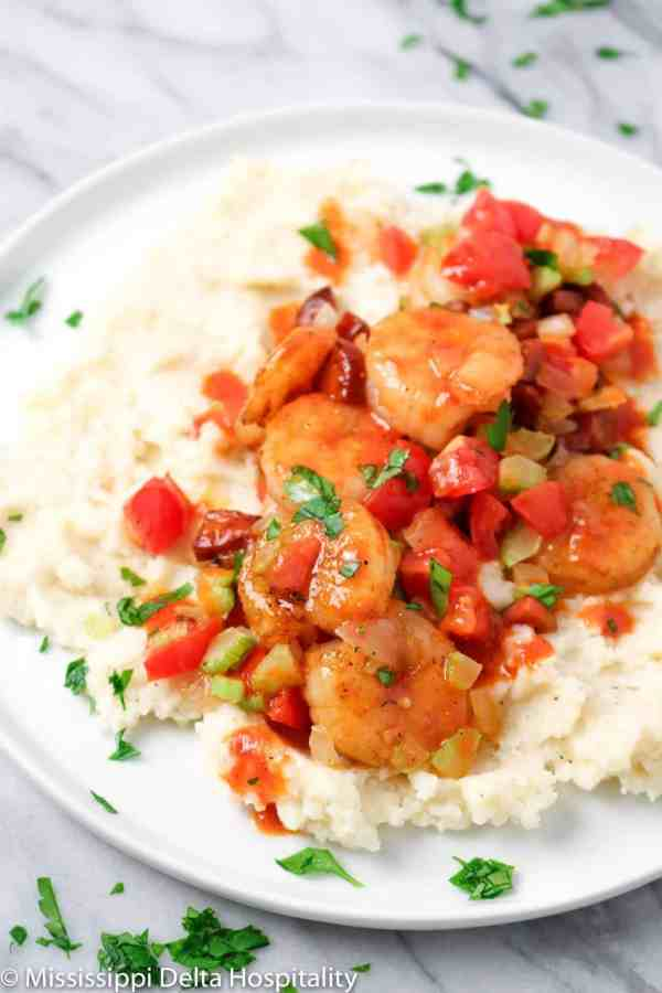 a white plate with shrimp and grits on a marble board.