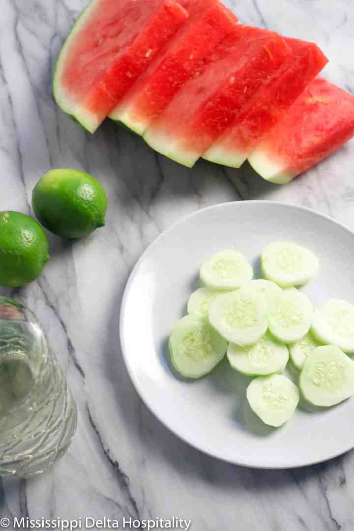 slices of watermelon, cucumber, whole limes, and simple syrup on a marble board