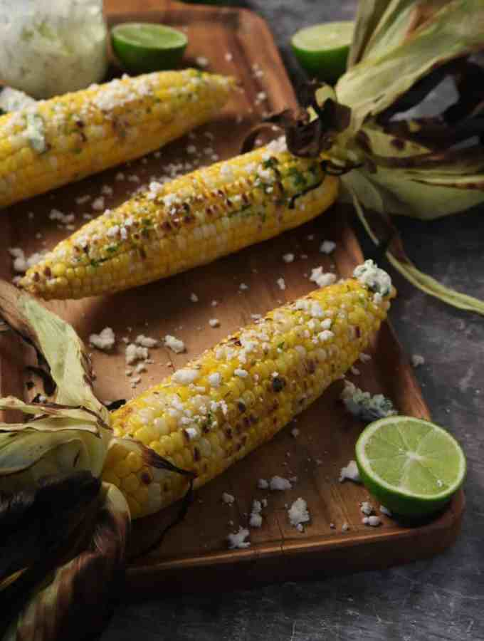 three ears of corn on a wood serving board with queso fresco sprinkled on top and lime slices