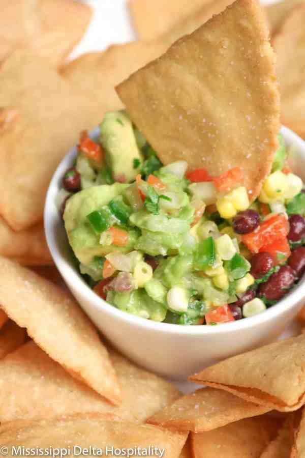 a bowl of guacamole with a homemade chip in it