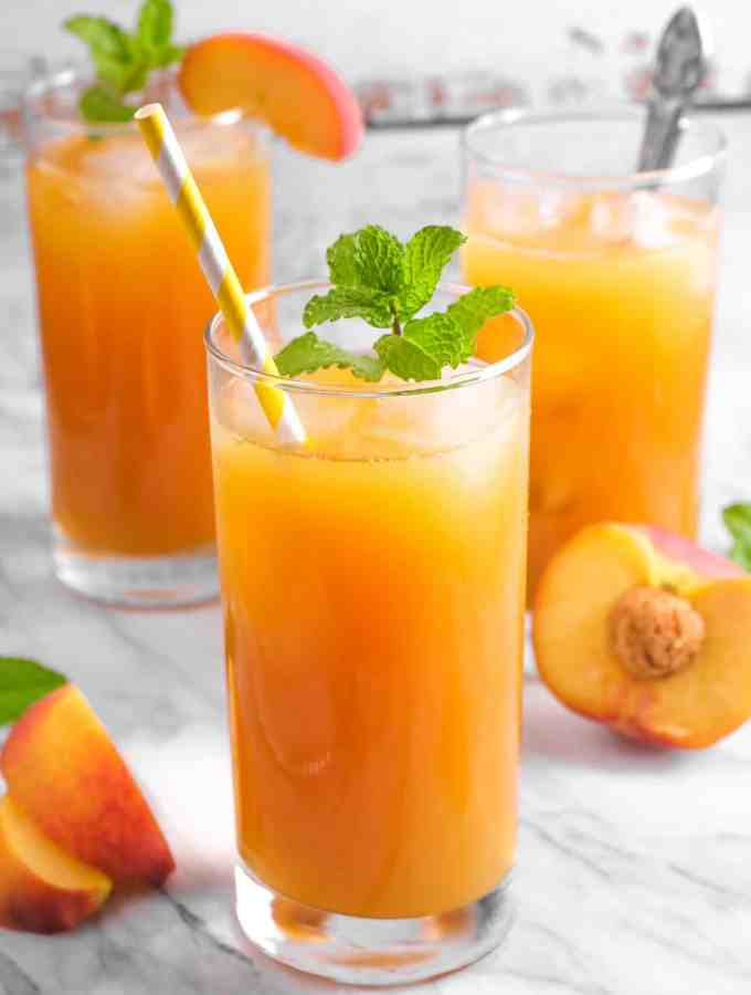 three glasses of peach iced tea on a marble board with mint and sliced peaches