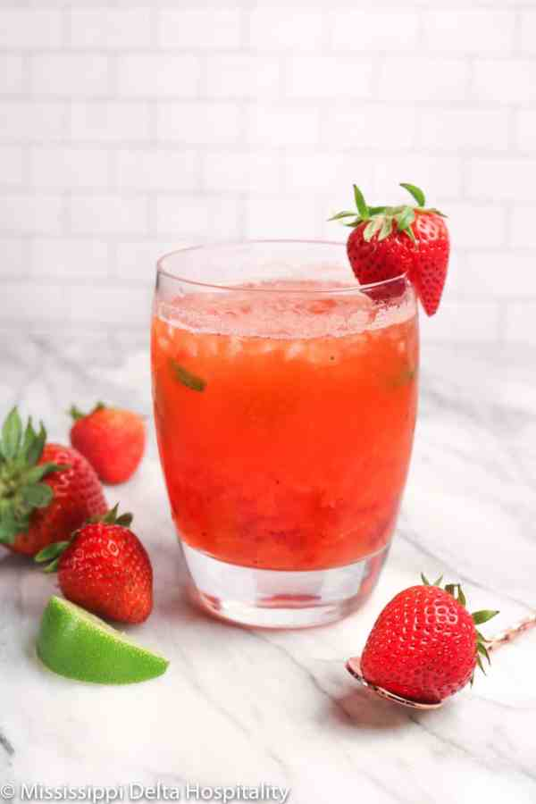 strawberry mint julep cocktail on a marble board with strawberries and lime slices