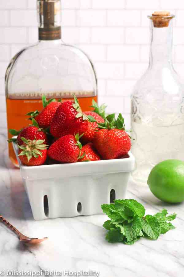 ingredients for strawberry mint julep on a marble board