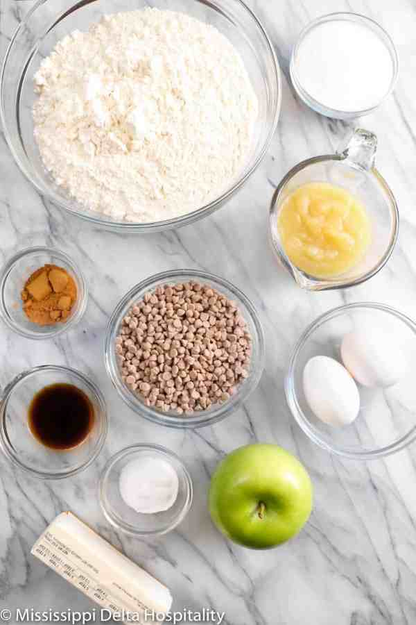 bowls of flour, sugar, apple sauce, cinnamon chips, eggs, vanilla, apple pie spice, butter, and baking powder on a marble board