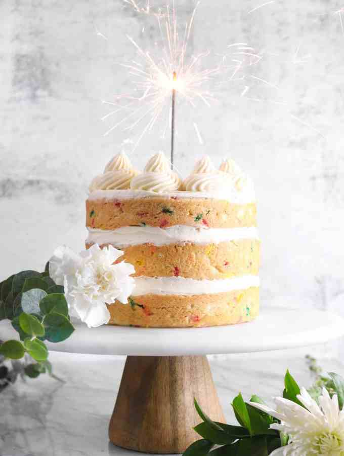 funfetti cake with a sparkler and white flowers on a marble cake plate
