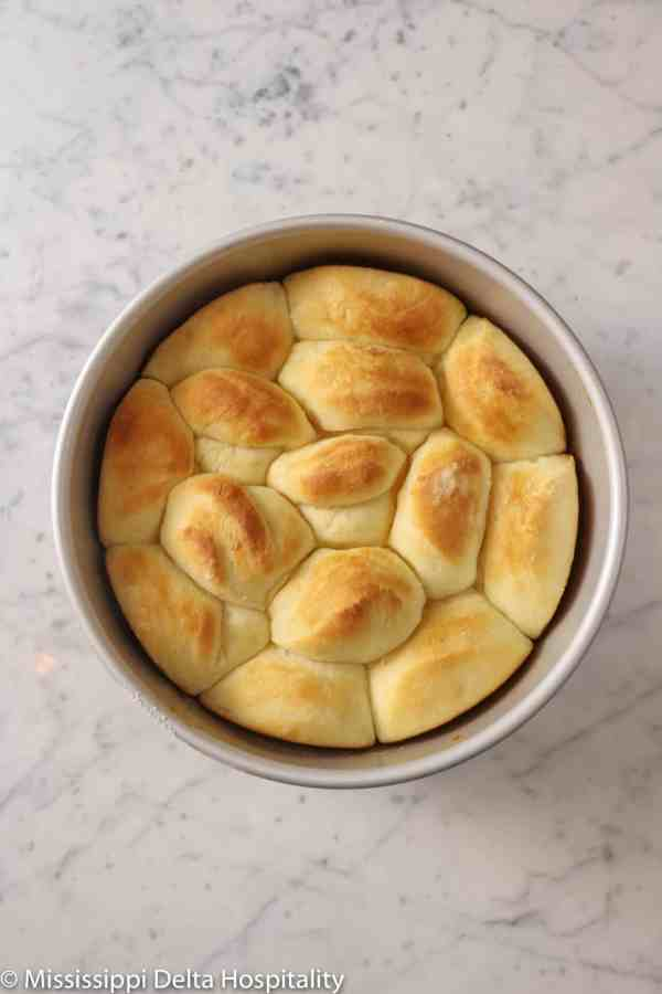 baked dinner rolls in a circle baking pan on a marble board