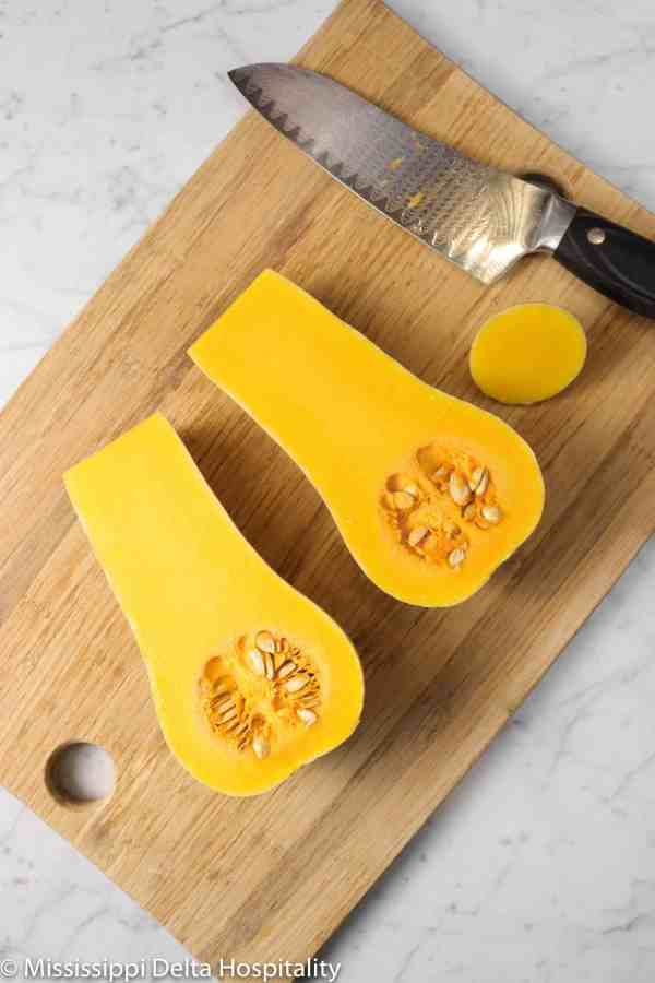 butternut squash cut in half on a cutting board
