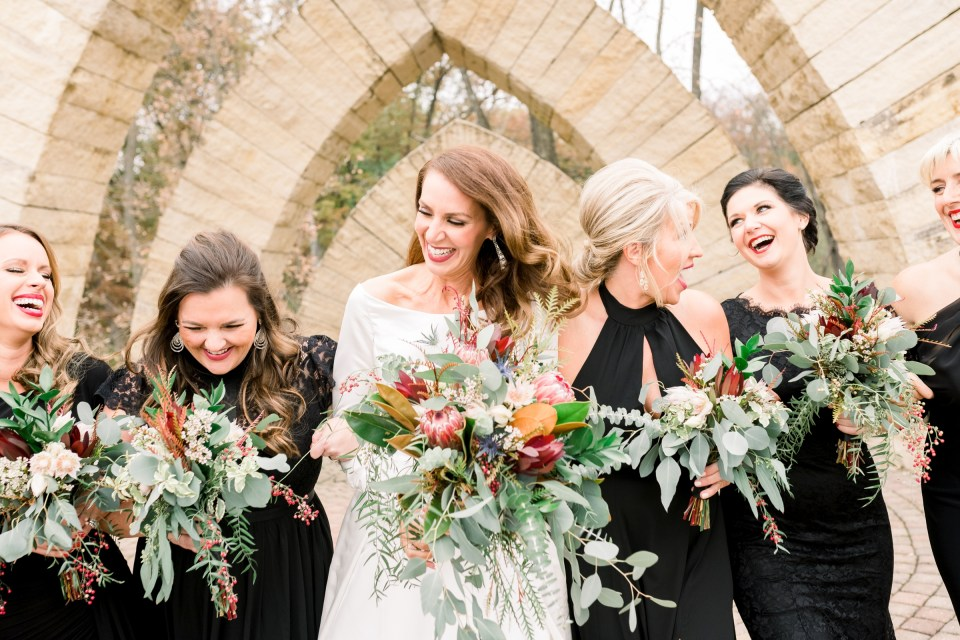 Bride in custom wedding dress by L'ezu Bridal Atelier of Beverly Hills and bridesmaids laughing