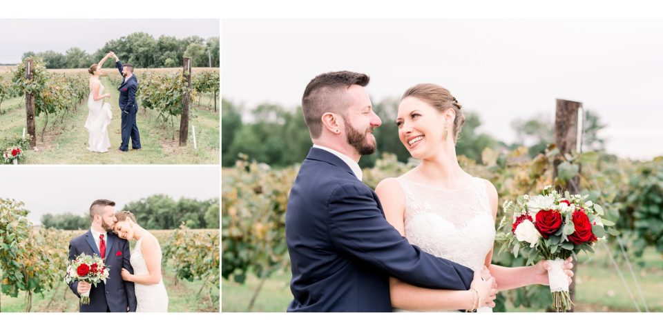 The bride and groom dancing in the vineyard while holding her bridal bouquet of red and white florals.