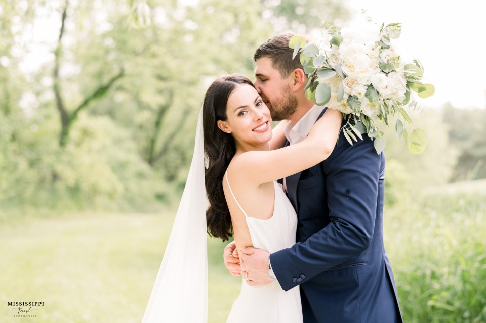 Bride and groom snuggling with bridal bouquet
