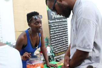 Tierra Williams, owner of Pesto's Vegetarian Cuisine and Catering, taking an order at the Juneteenth Festival on Farish Street.