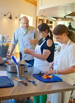 Executive Chef Matthew Sheeter give tips on fruit preparation to Ann Marie McGee, center, and Helen Ann Campbell Tuesday, June 7, at the Farmer's Table Cooking School in Livingston.
