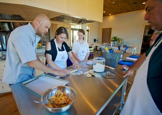 Executive Chef Matthew Sheeter give tips on dough preparation to Ann Marie McGee, center, and Helen Ann Campbell Tuesday, June 7, at the Farmer's Table Cooking School in Livingston.