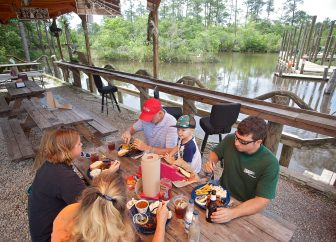 The Fontenot family from Mobile, Ala., eats lunch near the water at The Shed BBQ & Blues Joint in Ocean Springs.