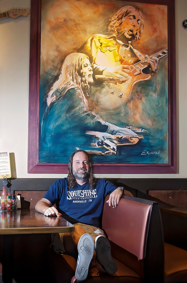 "Soulshine Pizza Factory owner Chris Sartin sits under one of the paintinga that helps set the tone at his chain of pizza restaurants, which he calls ""deer camp for hippies."""