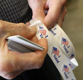 """A poll worker removes an """"I Voted"""" sticker to put on the lapel of a voter during Mississippi's primary election in March."""
