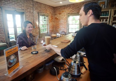 "College student Shelby Morace is served a caramel frappe at Steampunk Coffee Roasters by barista Robert Williams. ""I love coming here,"" Morace said. ""I always stop in when coming through Natchez."""