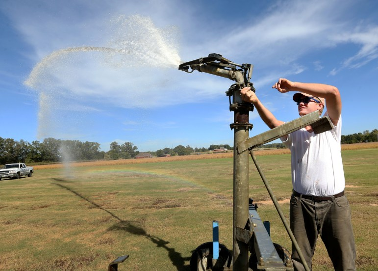 Kyle Downs, with Downs Sod Farm in Baldwyn, sets an irrigation sprinkler to water sod at his farm last month.