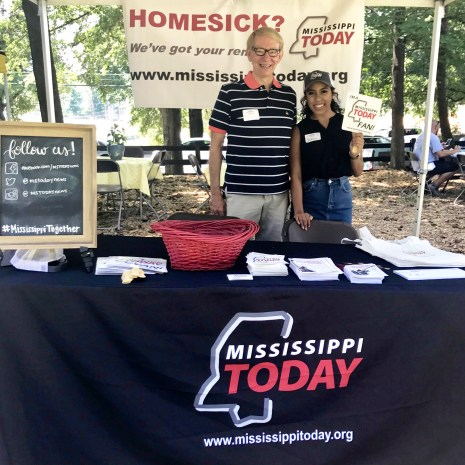 Mississippi Today Co-Editor Dennis Moore and Social Media Coordinator Sereena Henderson stand under their tent at the Mississippi Picnic in Chastian Park.