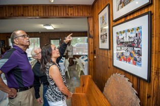 Bill Lester shows visitors artistic collages he has created at Dockery Farms