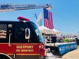 A Gulfport Fire Department truck ladder supports the U.S. flag and a sail at the Mississippi Aquarium groundbreaking in Gulfport.