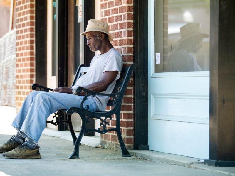 Man sits on bench. Utica. Mississippi