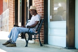Man sits on bench. Utica. Mississippi
