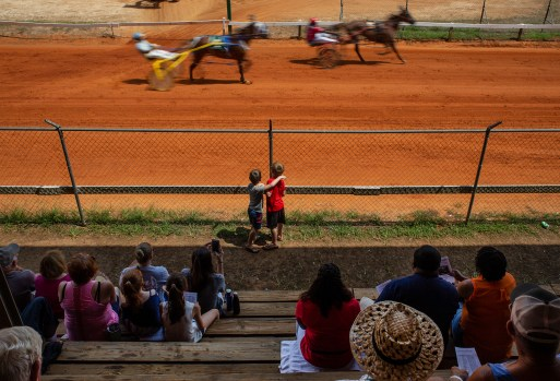 Fairgoers watch as racers compete during the harness racing competition at the Neshoba County Fair in Philadelphia, Miss. Thursday, August 2, 2018. The harness racing competition at the fair dates back to the early 1900s.