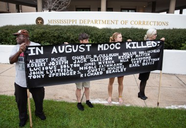 People hold a sign with the names of the 16 imates who died in state custody last month as they gathered outside of the Mississippi Department of Corrections Administrative building in downtown Jackson to protest Tuesday, September 12, 2018.