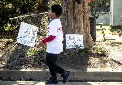 """A young child walks past a """"Justice for George"""" sign after a protest on Jones Avenue in Jackson Monday, January 21, 2019."""