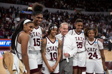 From left, Anriel Howard, Teaira McCowan, Jazzmun Holmes,coach Vic Schaefer, Zion Campbell and Jordon Danberry smile for a photo after their win against Clemson during their NCAA tournament game at Humphrey Coliseum.