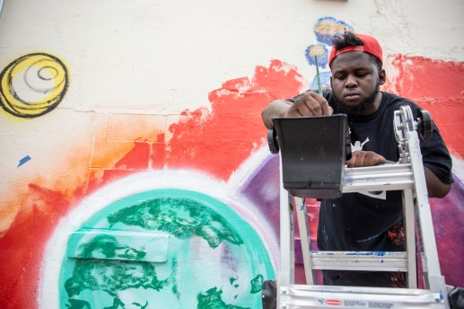 Kwame Braxton works on a mural as a part of Mural Fest in the 900 block of West Capitol Street in Jackson, Miss., Wednesday, April 17, 2019.