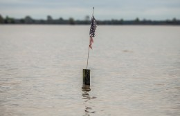 A tattered American flag attached to a post is surrounded by flood water in Issaquena County Friday, April 5, 2019.