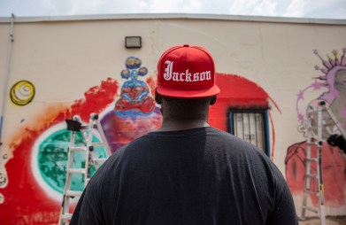 Artist and native Jacksonian Kwame Braxton takes a look at his mural painted on the Center for Community Production building in downtown Jackson Wednesday, April 17, 2019.