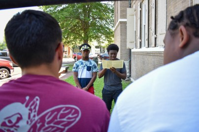 Student teachers Jules Gout (left) and Wood-May Joseph read an article detailing the tragedy of Emmett Till in Mississippi outside the courthouse where his trial took place in Sumner, Miss. on May 17.