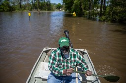 Anderson Jones Sr., 59, paddles through flood water to get the medicine that he left in his car in Fitler, Miss., Monday, April 15, 2019.