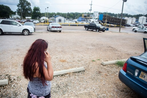 A family member makes a phone as she waits in hopes that her loved ones are released and returned to Koch Foods Inc., plant in Morton, Miss., Wednesday, Aug. 7, 2019. About 680 undocumented immigrants were detained during this a U.S. Immigration and Customs Enforcement raid at multiple locations across the state.