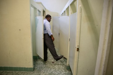 Principal Maurice Johnson looks at a broken toilets in one of the girl's bathroom at Leland Elementary School Monday, September 9, 2019.
