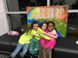 """Gracie Zimmerman (from left) Allison Craig and Aaliyah Labat share a moment after watching the first screening of """"The Hancock Community Quilt"""" in Kiln, at the Homegrown Literary & Arts Exchange. The painting behind them is by Greg Noll."""