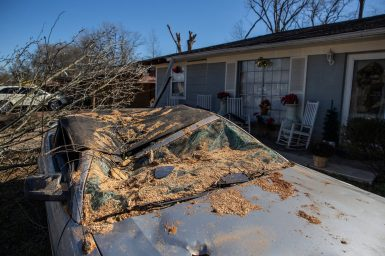 A damaged car is parked in the front yard of a residence on Ashcot Circle in Edwards, Miss., Thursday, December 19, 2019. A tree fell on the car during Monday's tornado.