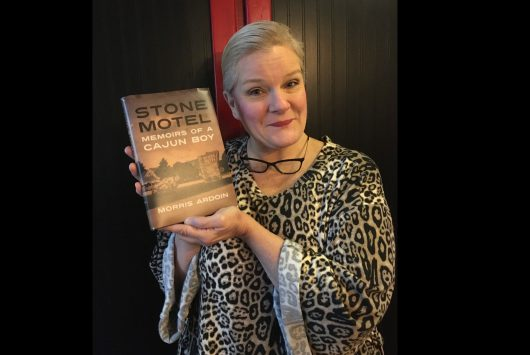 "Anne Eselin Bartin holds a copy of ""Stone Motel- Memoirs of a Cajun Boy,"" written by her friend and fellow writer, Morris Ardoin. Eslein said the book is great to read during the pandemic. The book is about Morris and his siblings living in their parents roadside motel during the 1960s and 1970s, staying out of trouble while coming in contact with all kinds of strange guests, playing canasta and Morris trying to steer clear of his abusive father. He found he could do this by visiting his loving Cajun grandparents with their thick Cajun French accents. They taught him about love and survival. Photo by Virginia Anne."