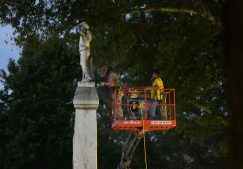 Workers move the Confederate statue located in the Circle at the University of Mississippi to an on-campus Confederate cemetery in Oxford, Miss. on Tuesday, July 14, 2020. (©Bruce Newman)