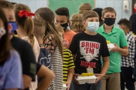 Students wait in line after receiving their lunch inside Neshoba County Central Middle School's cafeteria on the day of school on Wednesday, August 5, 2020 in Philadelphia, Miss.