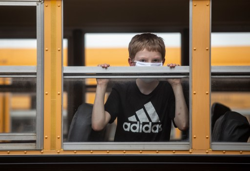 A Neshoba County School District student looks out the window of a school bus after the first day of school on Wednesday, August 5, 2020.