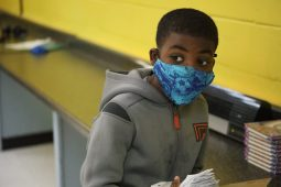 Josiah, a Jackson Public Schools student, stacks strips of notebook paper that his classmates at the Boys and Girls Club are pretending is money on Sept. 21, 2020. After they finish their school work for the day, they'll wait for their turn to use the gym.