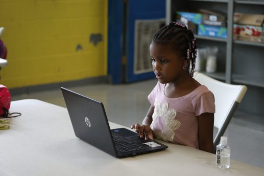 In a brief moment of concentration, Zen'Daiya examines her laptop before she returns to dancing throughout the classroom at the Boys and Girls Club Capitol Street unit on Sept. 21, 2020.