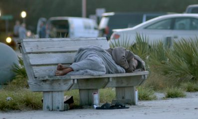 As a television crew sets up in the background, a homeless man gets more sleep at the Lighthouse Pier in Biloxi. The Mississippi Gulf Coast is bracing for Tropical Storm/Hurricane Sally.