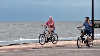 Two Mississippi Gulf Coast residents brave the high wind and surf to ride their bikes near Urie Pier in Gulfport. Hurricane Sally is now moving toward Mobile, Ala.