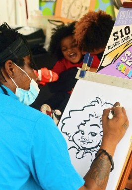 Caricature artist Taras McGirth of Charleston, South Carolina, applies the finishing touches to a portrait of Landan Fultz, 2 of Vicksburg.