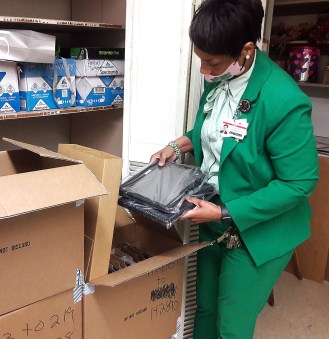 Powell Middle School Principal LaShunna McInnis looks over a delivery of 60 laptops at the school Tuesday. McInnis stated she expecting a delivery of 77 additional laptops for students. There are 424 students currently participating in virtual learning.